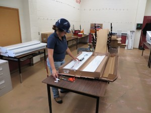 MaKayla getting ready to install new lighting in a classroom.